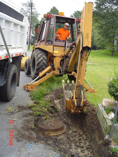A highway maintenance worker uses heavy equipment to work on the side of the road.