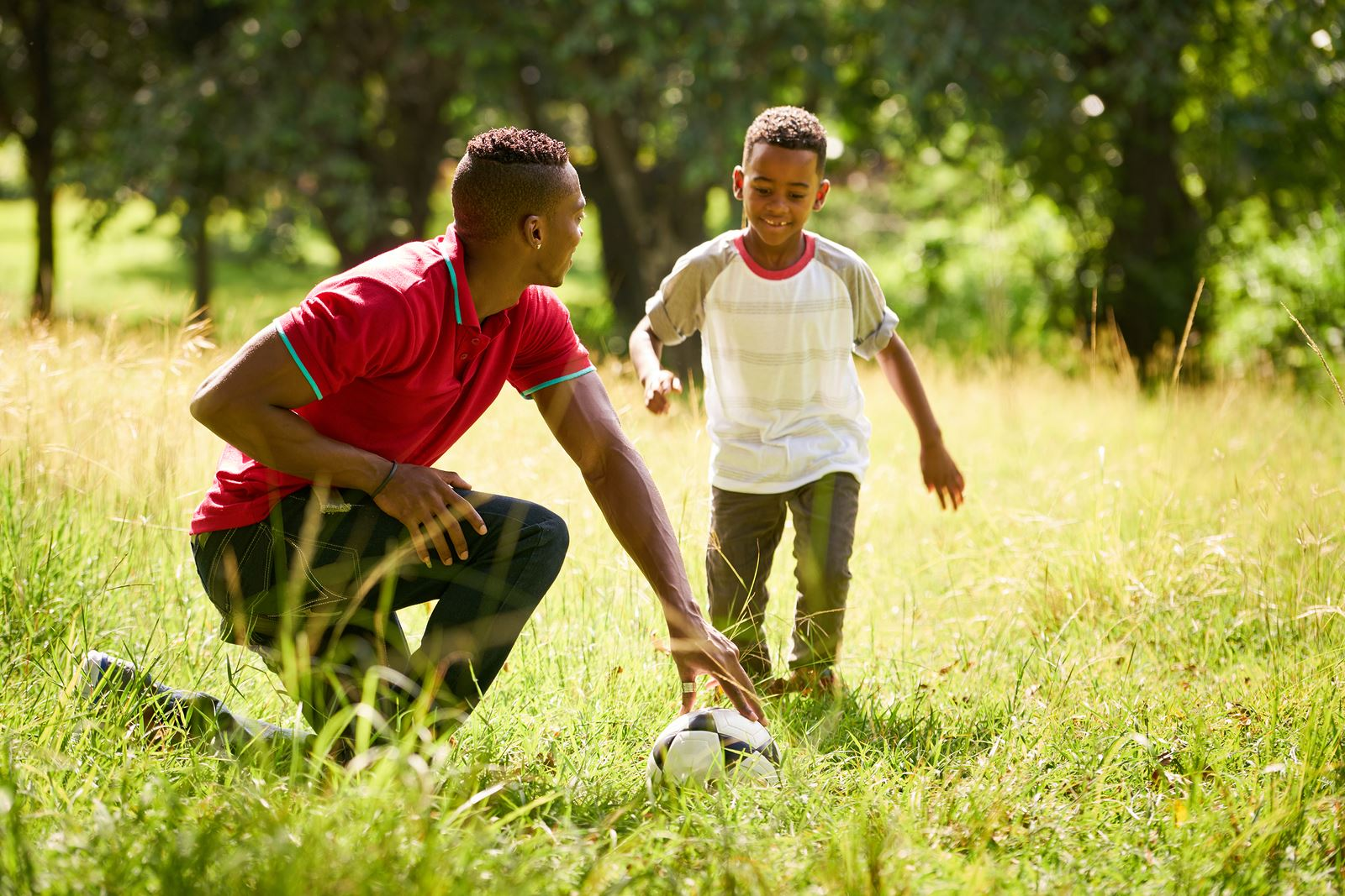 father teaching son with soccer ball
