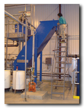 A worker stands on top a ladder and looks into a long blue piece of equipment.